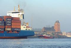 Heck eines Containerschiffs mit Schlepper auf der Elbe vor Hamburg Waltershof - Lotsenhaus Seemannshöft.