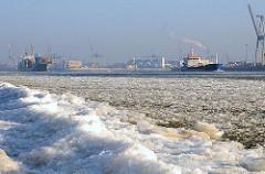 Eisbedeckter Elbstrand - Frachtschiffe laufen aus dem Hamburger Hafen - Elbe mit Eisschollen bedeckt.