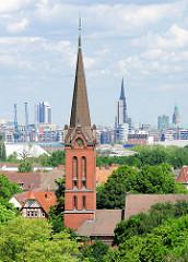 Kirchturm der ev. luth. Emmauskirche in Hamburg Wilhelmsburg - erbaut 1895, Architekt Hugo Louis. Im Hintergrund die St. Nikolaikirche und der Rathausturm.