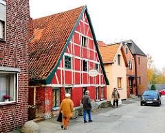 Historisches Fachwerkgebäude und Einzelhäuser in einer Seitenstrasse von Hamburg Finkenwerder.