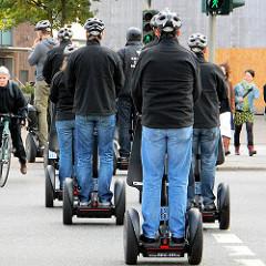 Stadtführung mit Segways - eine Gruppe SegwayfahrerInnen mit Helm auf einem Fussgängerüberweg in der Hamburger Altstadt.