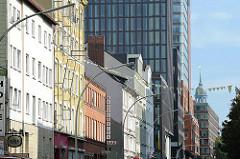 Alte und moderne Hausfassaden in der Bernhard Nocht Strasse in Hamburg St. Pauli - Spitze der St. Michaeliskirche im Hintergrund.