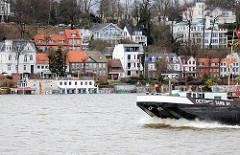 Ein Tankschiff fährt elbabwärts - im Hintergrund Häuser in Oevelgoenne von Hamburg Othmarschen - Sturmflutwarnung; das Wasser bedeckt den gesamten Strand.