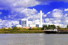 Heizkraftwerk Tiefstack im Hamburger Stadtteil Billbrook - im Vordergrund ein Binnenschiff auf der Norderelbe vor dem Elbufer bei Hamburg Rothenburgsort / Kaltehofe.