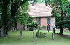 Kirchenschiff der Sinstorfer Kirche - Grabsteine zwischen hohen Bäumen.