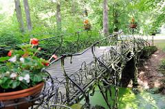 Eisernes Brückengeländer - Töpfe mit blühenden Pflanzen auf einer Brücke über einen Wassergraben auf dem Parkfriedhof in Hamburg Ohlsdorf.