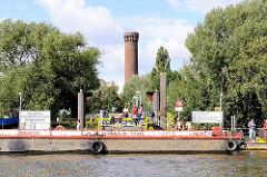 Anleger Entenwerder in Hamburg Rothenburgsort. Eine Schute hat am Ponton festgemacht, dahinter der Ziegelturm der Wasserspiele von Hamburg Rothenburgsort.