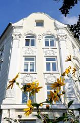 Hausfassade mit Stuck verziert - gelbe Blumen am Strassenrand; Impressionen aus dem Hamburger STadtteil Eimsbüttel.
