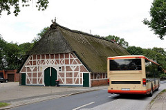 Historische Archtiektur Hamburgs - Fachwerkscheune mit Reet gedeckt. Autobus auf der Francoper Strasse.