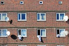 Hausfassade - Klinkerfassade (Ziegelfassade); Wohnhaus auf der Veddel in Hamburg. Satelittenschüsseln und Wäsche zum Lüften aus dem Fenster gehängt.