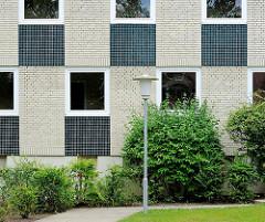 Architekturstile Hamburgs - Wohnblock in Hamburg Marmstorf - kubisches Mosaikdekor; Lampe im Stil der 1960er Jahre.