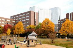Spielplatz auf dem Gelände der ehem. Gaswerks in Hamburg Barmbek Süd - Bürohochhaus und kleine Holzhäuser im Sand - Bäume mit farbigem prächtigem Herbstlaub.
