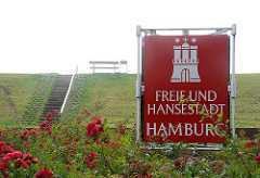 rotes Schild mit Wappen der Freien und Hansestadt Hamburg - Treppe auf den Deich - Sitzbank auf dem Deich von Neuwerk.