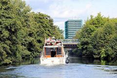 Fahrt im Schleusengraben - ein Motorboot fährt Richtung Hamburg Bergedorf - im Hintergrund das Hochhaus am Bergedorfer Hafen.