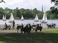Sommer in Hamburg - Segelboote auf dem Wasser - Hamburger und Hamburgerinnen in der Sonne auf Parkbänken am Alsterufer.