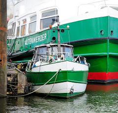 Eine alte HADAG - Fähre Altenwerder und ein Motorboot im Hafen von Hamburg Finkenwerder.