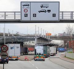 Einfahrt Zollstation Waltershof - Freihafengrenze; Lastwagen fahren auf die Grenzstation; Schilder weisen den Weg - im Hintergrund Fahrzeuge auf der Auffahrt zur Köhlbrandbrücke.
