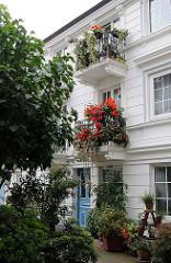 Hinterhofhaus in Hoheluft-Ost - weisses Wohnhaus, Balkons mit roten Geranien in der Hegestrasse.
