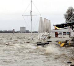 Das Hochwasser überspült den Elbstrand in Hamburg Oevelgönne; die Sonnenschirme sind zusammengefaltet,