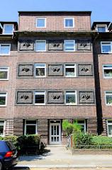 Fassade eines mehrstöckigen Klinkergebäudes - Terrakottaplatten als Dekor  - Architektur in Hamburg BArmbek Nord.