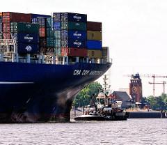 Containerschiff CMA CGM ANDROMEDA mit Schlepper auf der Elbe - im Hintergrund das Lotsenhaus am Seemannshöft von Hamburg Waltershof.