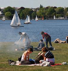 Grillspass im Sommer am Alsterufer - der Grill qualmt über die Wiese - Segelschiffe im Hintergrund.