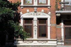 Historische Ornamente um ein Fenster eines mehrstöckigen Wohnhauses an der Barmbeker Strasse Winterhudes.