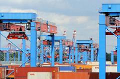 Containerkräne auf dem Lagergelände des HHLA Container Terminals Altenwerder - Portalkranpaare DRMG bei der Arbeit; Ein Portalkranpaar (Double Rail Mounted Gantry – DRMG)lädt den Container zur Zwischenlagerung ab. Das DRMG besteht aus zwei unabhängig