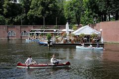 Kanus auf dem Goldbekkanal - Gäste im Café auf dem Ponton geniessen am Wasser die Aussicht und die Sonne.