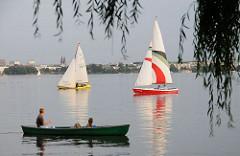 Am Alsterufer der Bellevue fährt ein Ruderboot - Segelboote keuzen auf de Aussenalster.