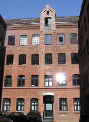 Hinterhof in Hamburg Sternschanze - historisches GEwerbegebäude aus rotem Ziegel mit Winde unter dem Dach.
