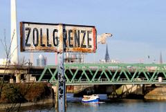 Schild Zollgrenze; Hamburger Freihafengrenze am Reiherstieg - eine Barkasse der Hafenrundfahrt fährt Richtung Ellerholzschleuse.