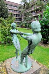 Bronzeskulptur Tanzende Mädchen - Innenhof mit Sträucher im Hamburger Stadtteil Dulsberg.