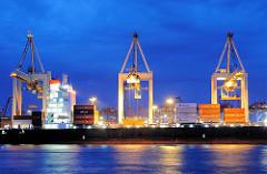 Beleuchtete Containerbrücken fertigen ein Containerfrachter am Containerterminal Burchardkai an der Elbe im Hamburger Hafen ab.