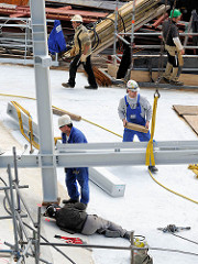 Bauarbeiter arbeiten im Juli 2013 auf dem Dach der Baustelle der Hamburger Elbphilharmonie - Eisenträger werden zusammengeschweisst.