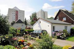 Einzelhäuser mit Vorgarten und Autoauffahrt - blühende Blumen; Hochhäuser im Hintergrund - Fotos aus dem Stadtteil Hamburg Lohbrügge.