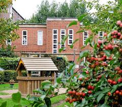 Innenhof mit Spielplatz - Sträucher mit Herbstfrüchten - Hamburger Architektur - Wohnanlage Jarrestadt.