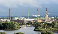Einfahrt zum Peutehafen - dahinter Industriegebäude auf der Peute, rauchende Schornsteine und Industrieschlote.