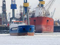 Hamburg im Winter - Schiffe im Eis - die Elbe im Hamburger Hafen ist mit Eis bedeckt, ein Schiff bahnt sich seinen Weg durch die Eisschollen.