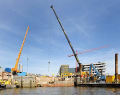 Baustelle an einer Kaimauer im Magedeburger Hafen - Stadtteil Hamburg Hafencity; hohe Auslegerkräne - im Hintergrund die Baustelle der Hafencityuniversität.