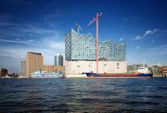 Baustelle der Elbphilharmonie an der Elbe - Stückgutfrachter KARELIA und ein Fahrgastschiff / Raddampfer Louisana in Fahrt - lks. die Bürogebäude an der Kehrwiederspitze.