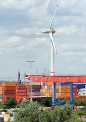 Containerlager und Portalkran auf dem Terminalgelände von Hamburg Altenwerder - im Hintergrund hinter den hoch gestapelten Metallboxen ragt der Kirchturm der ST. Gertrudkirche heraus, daneben eines der beiden Windkraftanlagen, die zu den höchsten Bau