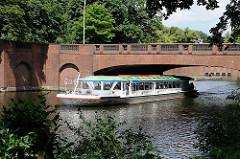 Ein Schiff der Weissen Flotte der Alstertouristik fährt unter der Stadthallenbrücke hindurch.