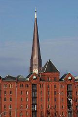 Kirchturm der Hamburger St. Jakobikirche hinter den roten Backsteingebäuden der Hamburger Speicherstadt.