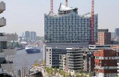Neubauten am Grasbrookhafen in der Hafencity - entstehende Albphilharmonie mit Glasfassade - Frachtschiff auf der Elbe.