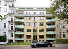 Jahre Architektur / Hamburg Winterhude, Sierichstrasse; Wohnhaus mit gelber Klinkerfassade und mintgrünen Mosaik-Balkons.