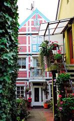 Hinterhaus, Fachwerkhaus mit blau abgesetzten Fachwerk und roter Hausfassade.