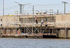 Ausbesserung der Kaimauer am Versmannkai im Hamburger Baakenhafen - schwimmender Ponton mit Baugerüst.