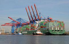 Ein Containerschiff legt mit Hilfe von Schleppern unter der Containerbrücke des HHLA Terminals Burchardkai an.
