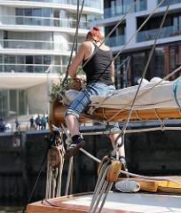Eine Seefrau arbeitet auf einem der Traditionsschiffe in der Hafencity - moderne Architektur im Hintergrund.